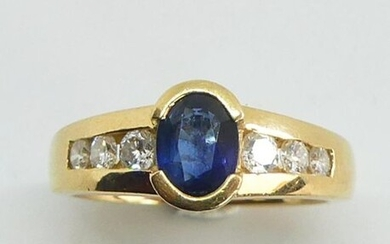 RING in yellow gold set in a half-closed setting with a facetted oval sapphire, the setting enhanced on either side by a line of diamonds. Gross weight 6.79 g TDD 51