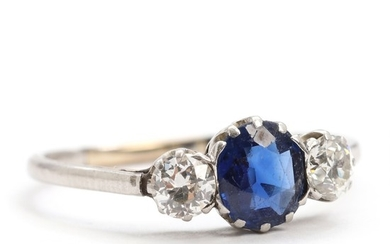 Sapphire and diamond ring set with a faceted sapphire flanked by two old mine-cut diamonds, mounted in 18k white gold. Size 65. Circa 1910.