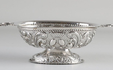 Silver brandy bowl, 934/000, decorated with gear and acanthus leaves. Equipped with 2 horizontally placed handles with coat of arms engraving. The bowl is placed on an oval base. MT .: A. De Haas, Sneek. Equipped with pseudo-proofs, manufactured for...