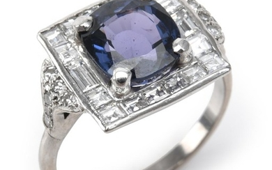 A SPINEL AND DIAMOND RING - Of Art Deco style, featuring a cushion cut blue spinel weighing an estimated 3.50cts, within a border of...