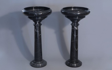 A pair of black gray marble pedestals with...