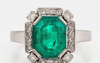 An 18K white gold ring set with a faceted emerald and round brilliant-cut diamonds