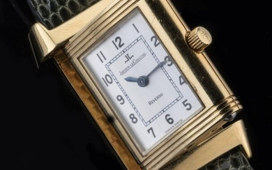 JAEGER-LECOULTRE. WATCH BRACELET model REVERSO LADY. Ladies' watch in yellow gold 750 thousandths. The reversible case reveals a white enamelled dial showing the hours in Arabic numerals around a railway. Blued steel sword hands. The inside of the...