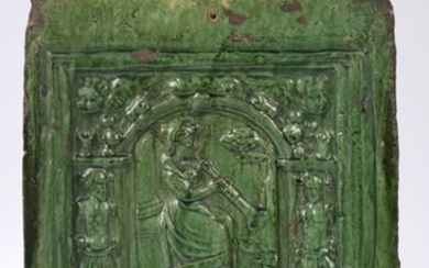 Pink earthenware stove tile with a green glazed...