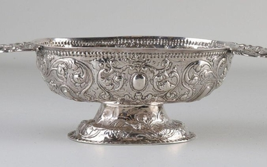 Silver Frisian brandy bowl with driven floral images on an oval base and flat ears. Inscription SS 1766. 25x11x7cm. about 230 grams. Equipped with a certificate from the inspection chamber of Dokkum, last: P:1750. In good condition.