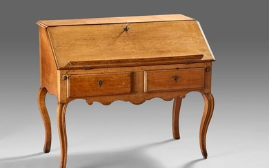 Sloping oak desk opening to a flap revealing lockers and drawers, two drawers in belt.
