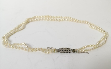 Two row necklace of graduated pearls, on diamond set snap.