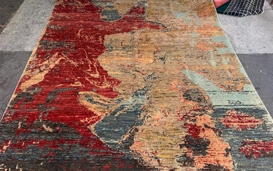 A CONTEMPORARY STYLE RUG IN PIXELATED DESIGN IN TONES OF RED, YELLOW AND GOLD