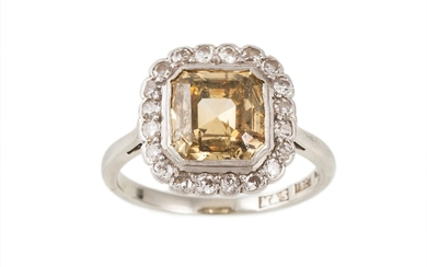 A DIAMOND CLUSTER RING, the emerald cut yellow diamond to a ...