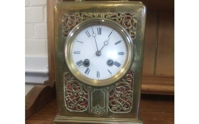 A French brass mantel clock, with scrolled and pierced decor...