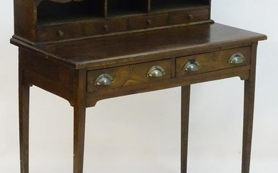 A late 19thC oak writing desk with a moulded top