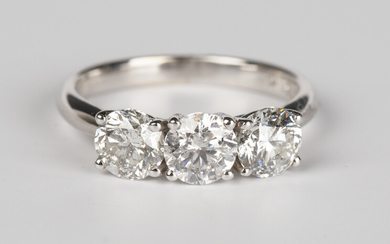 A white gold and diamond three stone ring, claw set with a row of circular cut diamonds, detailed