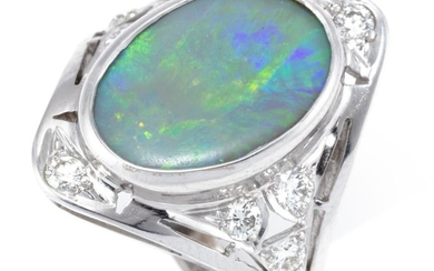 AN 18CT WHITE GOLD NOUVEAU STYLE OPAL AND DIAMOND RING; rub set with a 15.5 x 10.5mm opal doublet, ends and shoulders set with 8 rou...