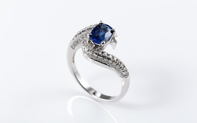 AN 18CT WHITE GOLD SAPPHIRE AND DIAMOND RING; bypass mount centring an approx. 1.00ct blue oval sapphire between shoulders set with...