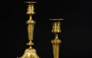 Pair of gilt bronze torches, the fluted shaft resting on a circular base with scraps of piastres and engraved garlands. Probably Northern Europe early 19th century. H : 26,5 cm