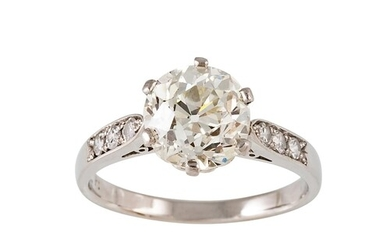 A DIAMOND SOLITAIRE RING, the old cut diamond flanked by dia...