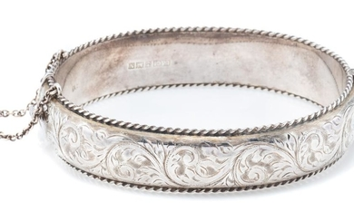 A HALLMARKED STERLING SILVER HINGED BANGLE; 1.5cm wide hollow bangle with engraved scrolling decoration to front and applied wire tw...