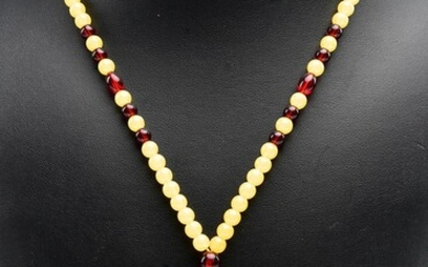 A RECONSTITUTED CARVED AMBER PENDANT NECKLACE