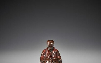 AN EARLY LACQUERED WOOD NETSUKE OF A MAN WITH HIBACHI