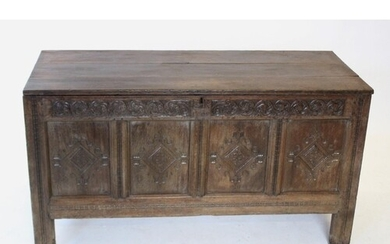 An early 17th century oak coffer, the hinged plank cover car...