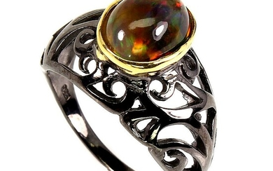 An opal ring set with a cabochon opal, mounted in black rhodium plated sterling silver. Size 56.