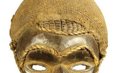 Dark stained wood mask, a cord underlines the...
