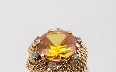 Gold ring set with a synthetic yellow sapphire...