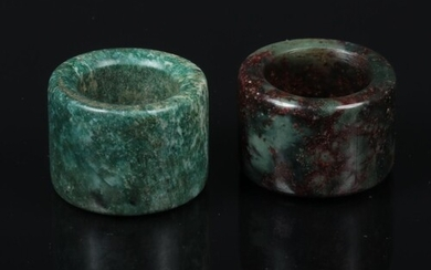 Two Chinese carved jade coloured hardstone archers rings, on...