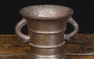 A Late 17th or Early 18th Century Cast Bronze Mortar. The heavily pitted flared body with raised rin