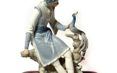 A Lladro model of an Indian figure and a peacock...