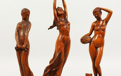 A SET OF THREE CARVED WOOD STANDING FEMALE FIGURES.