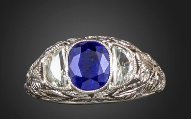 A sapphire and diamond three stone ring, the oval-shaped sapphire is flanked with demi-lune shaped diamonds in a pierced foliate engraved platinum shank, size L