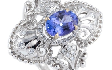 AN 18CT WHITE GOLD TANZANITE AND DIAMOND RING; Edwardian inspired design centring an oval cut tanzanite of approx. 0.92ct to surroun...