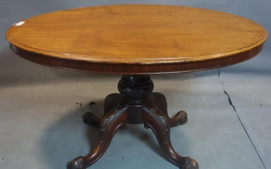 An oval mahogany dining table, on turned support and scrolli...