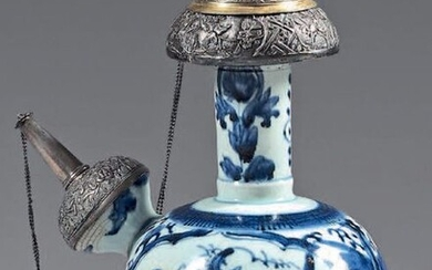 Kendi in Japanese porcelain with silver and silver-gilt frames. 17th century porcelain, silver 900°/°° silver mounts, foreign work. With blue-white decoration of landscapes in reserves, flowers on the neck, cracks.