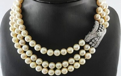 Necklace of three rows of cultured pearls from 8 to 8,5 diam. approx. enhanced with a 750°/°° white gold and platinum clasp centered with a diamond set in a large diamond cross pavé, circa 1960, Gross weight: 118g