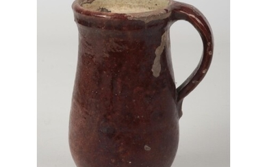 A 17th century brown glazed earthenware mug with plain strap...