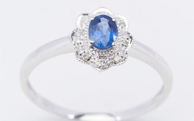 A SAPPHIRE AND DIAMOND CLUSTER RING IN 18CT WHITE GOLD, CENTRALLY SET WITH AN OVAL CUT BLUE SAPPHIRE WEIGHING 0.70CT, WITHIN A DIAMO...