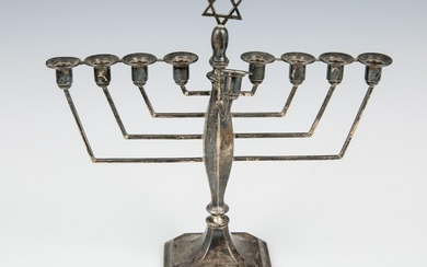 A STERLING SILVER MENORAH. London, 1920's. On a square...