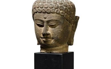 A large Javanese Buddha head carved in volcanic rock
