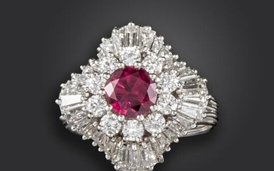 A ruby and diamond cluster ring, the circular-cut ruby set within a surround of circular-cut diamonds and further border of undulating tapered baguette-shaped diamonds in platinum, size O