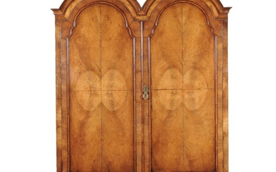 A walnut double domed wardrobe in early 18th century style