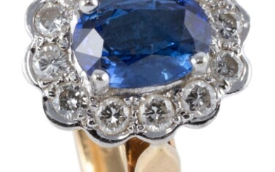 AN 18CT GOLD SAPPHIRE AND DIAMOND CLUSTER RING; centring a fine blue oval cut sapphire of approx. 1.1ct surrounded by 12 round brill...