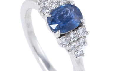 AN 18CT WHITE GOLD SAPPHIRE AND DIAMOND RING; centring a 1.24ct fine blue oval Ceylon sapphire between shoulders set with 12 round b...