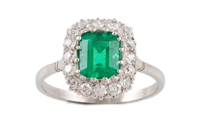 AN EMERALD AND DIAMOND CLUSTER RING, with one rectangular st...
