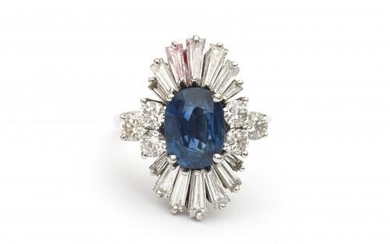 An 18 carat white gold sapphire and diamond cluster ring. Featuring an oval cut blue sapphire of ca. 2.40 ct. surrounded by fourteen baguette cut tapered diamonds and six brilliant cut diamonds, in total ca. 2.90 ct., ca . G-H, ca. VS. Gross weight:...