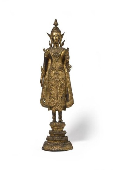 THAILAND A gilded lacquered bronze figure representing a standing Buddha resting on a quadruple base inlaid with mica. Late 19th century Height : 52.5 cm
