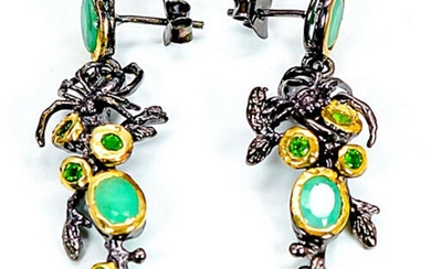A pair of ear pendants each set with nummerous oval and circular-cut emeralds and chrome diopsides, mounted in black rhodium and gold plated sterling silver.