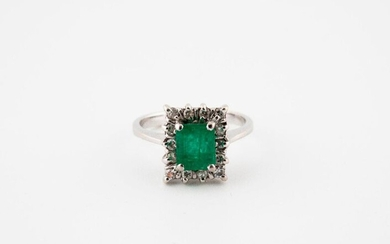 A white gold ring (750) centered by a rectangular emerald in a setting of small brilliants, in claw setting.