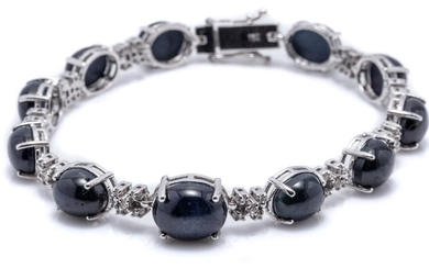 AN 18CT WHITE GOLD SAPPHIRE AND DIAMOND BRACELET; composed of 11 links each set with a cabochon blue star sapphire united by 10 clus...